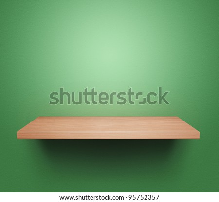Empty wooden shelf at the green wall - stock photo