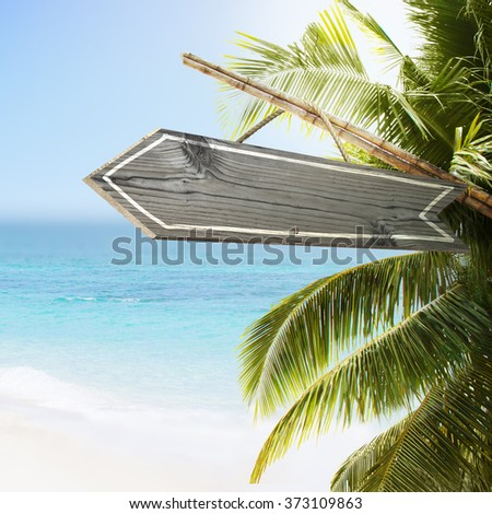 Empty wooden sign on tropical white sand beach summer background. Lush tropical foliage and sunshine. Blue ocean at perfect day. No people. - stock photo