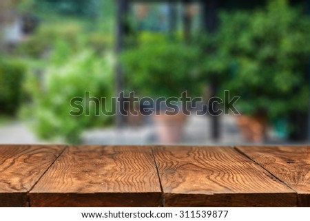 Empty wooden table against summer backyard or patio with green plants on background - stock photo