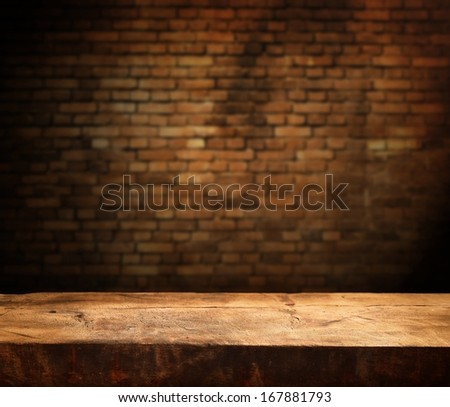 Empty wooden table and brick wall in background - stock photo