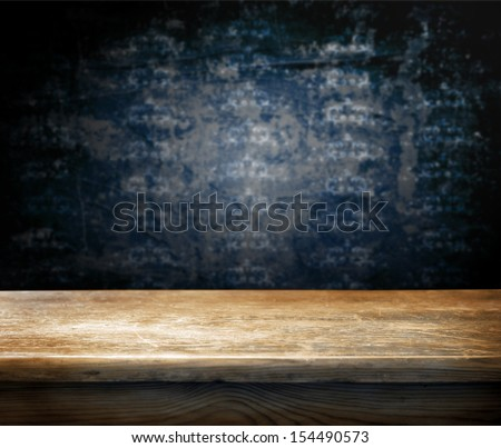 Empty wooden table and dark blue wall with ornaments in background - stock photo
