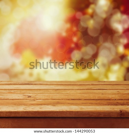 Empty wooden table over autumn leaves bokeh background. Ready for product montage - stock photo