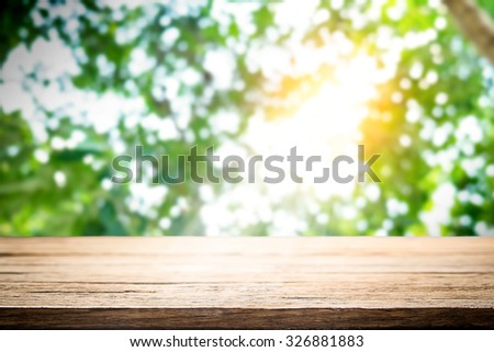 Empty wooden table platform over Nature bokeh garden background for presentation product. - stock photo