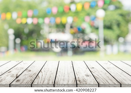 Empty wooden table with blurred party on background - stock photo