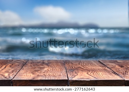 Empty wooden table with blurred sea on background, natural background with bokeh - stock photo