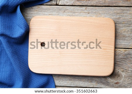 Empty wooden table with cutting board and napkin on grey background - stock photo