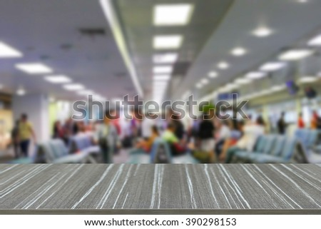 empty wooden table with people at the gate inside the airport building blur background for displaying your product - stock photo