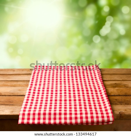 Empty wooden table with tablecloth over bokeh background - stock photo