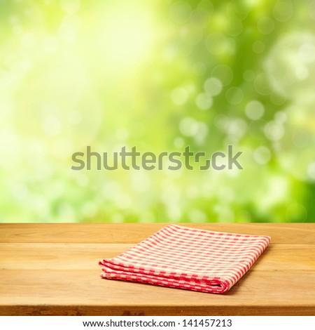 Empty wooden table with tablecloth over garden bokeh background - stock photo