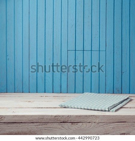 Empty wooden white table with tablecloth over blue wooden wall. Kitchen background - stock photo