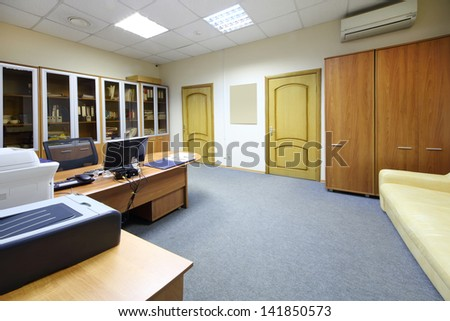 Empty working area with desktop, bookcase and sofa in modern office. - stock photo