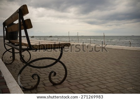 Empty wrought iron bench with wooden seat and back on a deserted promenade overlooking the sea in cloudy weather in the cold season - stock photo