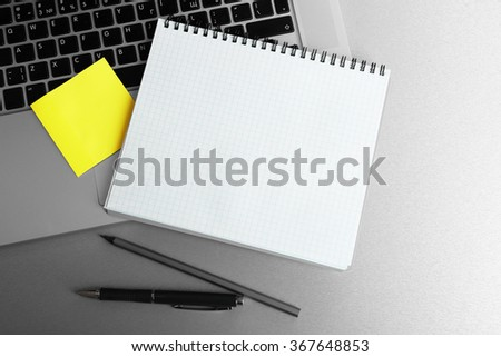Empty yellow adhesive paper, notebook on laptop keyboard, pen and coffee cup on desk background - stock photo