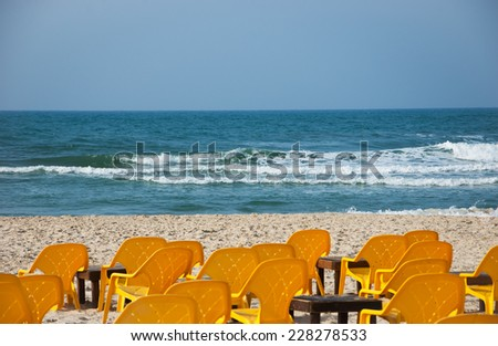 Empty yellow chairs and wooden tables on the sandy beach (Tel Aviv, Israel) Selective focus on the sea waves. - stock photo