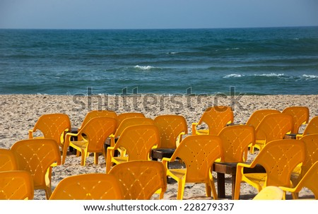 Empty yellow chairs and wooden tables on the sandy beach (Tel Aviv, Israel) Selective focus on the first row of chairs and the sand. - stock photo
