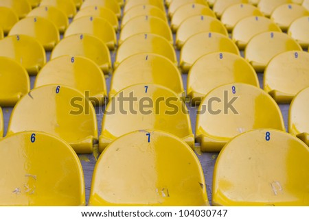 Empty yellow football stadium seats are creating a symetric view - stock photo