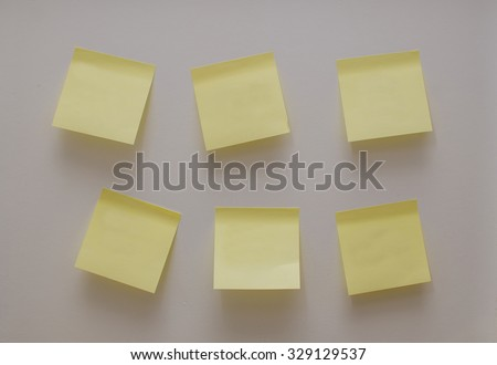 Empty yellow note sticks on the white wall office background - stock photo