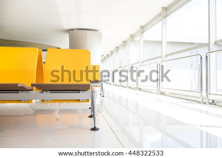 Empty yellow plastic seats near windows on airport terminal use for passenger waiting entrance to the gate.Image use sun light flare effect and vintage color tone. - stock photo