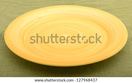 empty yellow plate on a green textured background - stock photo