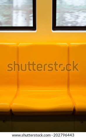 Empty yellow seats and windows in train - stock photo