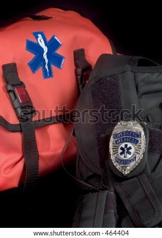 EMT medical bag, tactical vest and EMS shield badge - stock photo