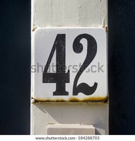 enameled house number forty two. Black lettering on a white background. - stock photo