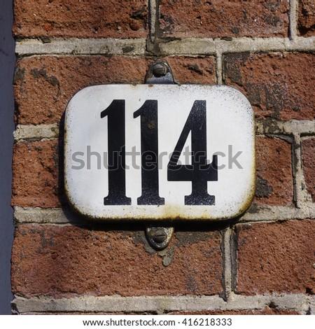 Enameled house number one hundred and fourteen. - stock photo