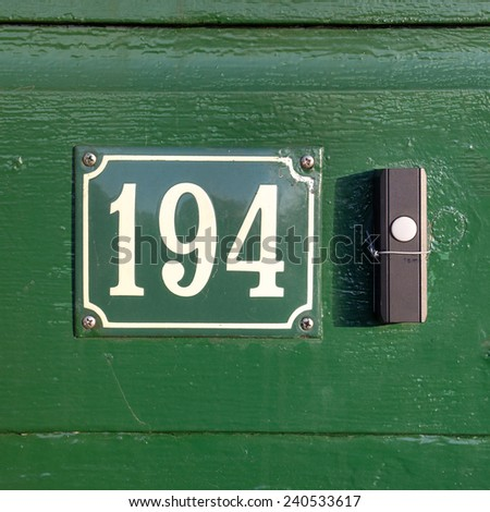 enameled house number one hundred and ninety four, next to a doorbell - stock photo