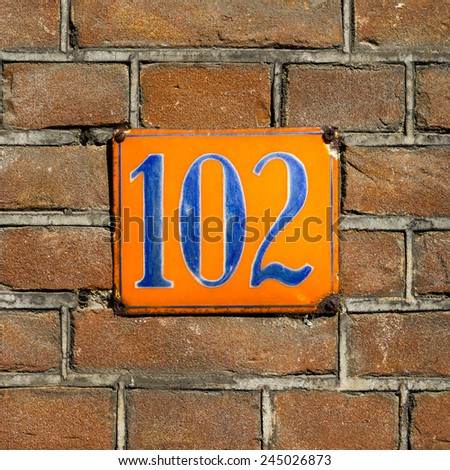 enameled house number one hundred and two - stock photo