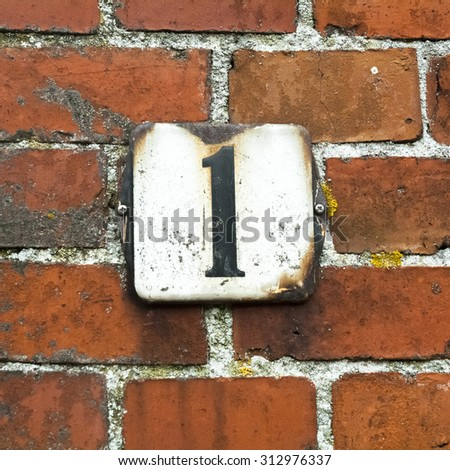 enameled house number one on a red brick wall. - stock photo