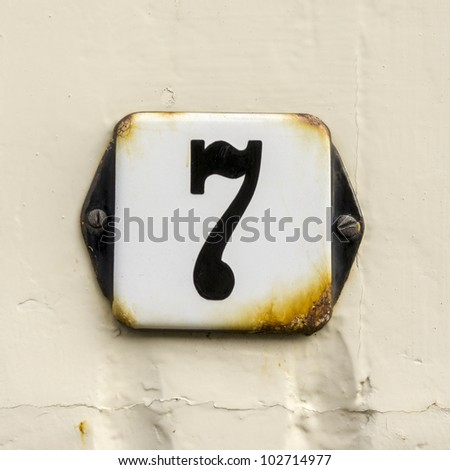 enameled house number seven. the edges starting to rust - stock photo