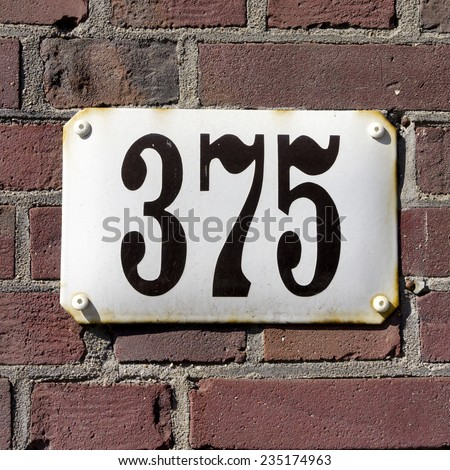 enameled house number three hundred and seventy five - stock photo