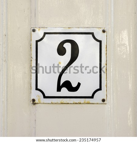 Enameled house number two. Black numeral on a white background - stock photo