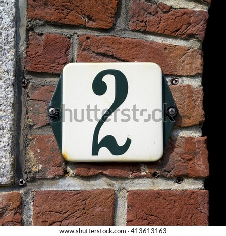 enameled house number two, green numeral on a white background. - stock photo