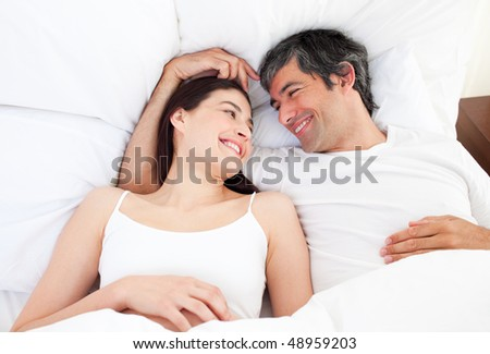 Enamored couple hugging lying in their bed at home - stock photo
