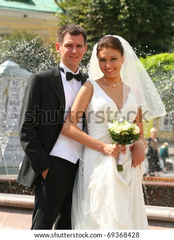 Enamoured groom and the bride against a fountain. - stock photo
