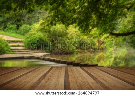 Enchanted forest scene of slow flowing stream with vibrant reflections with wooden planks floor - stock photo