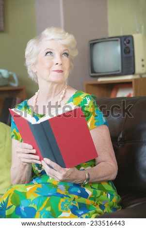 Enchanted woman with grin reading a book - stock photo