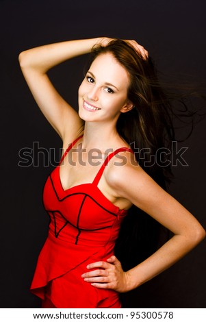 Enchanting lively young woman in a sexy red dress with a beaming radiant smile. - stock photo