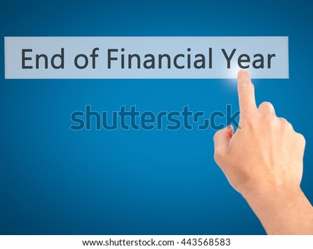 End of Financial Year - Hand pressing a button on blurred background concept . Business, technology, internet concept. Stock Photo - stock photo