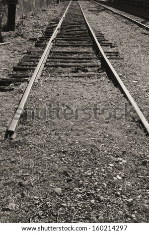 End of the Line - Abandoned Factory Train Tracks - Old Out of Service Obsolete Train Tracks End Abruptly - stock photo