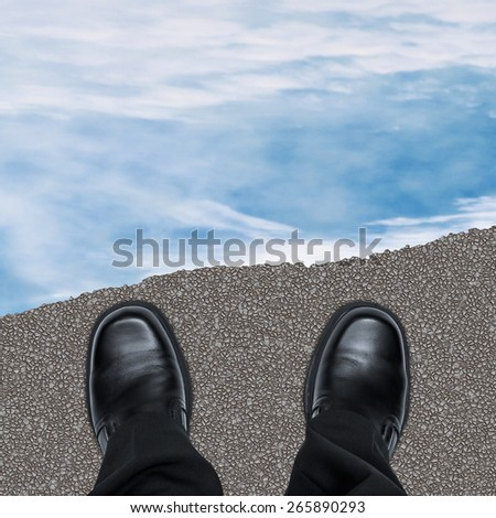 End of the road concept with business man shoes on road against cloudy sky, overhead view - stock photo