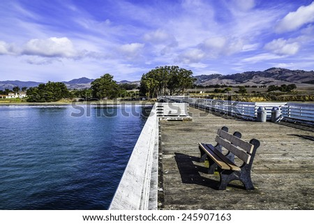End of the San Simeon Pier with empty bench, and Hearst Castle in the background on the California Central Coast, near Cambria, CA.  - stock photo
