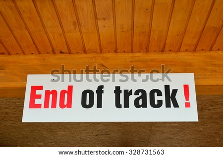 End of track warning sign written in red and black letters hanged on a wooden ceiling - stock photo
