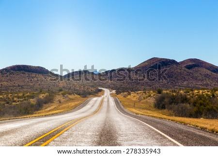 endless asphalt road with blue sky - stock photo