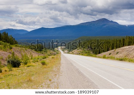 Endless empty road of Alaska Highway, Alcan, crossing wide open expanse boreal forest taiga landscape west of Watson Lake, Yukon Territory, Canada - stock photo
