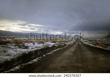 Endless icy roads through a snowy landscape in Iceland - stock photo