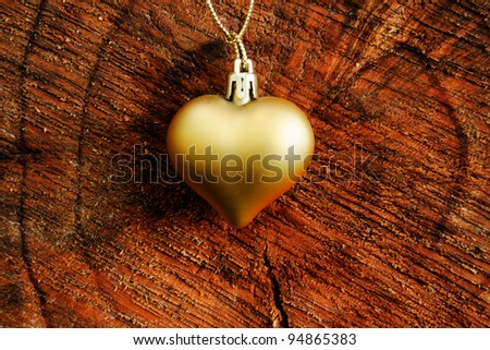 Endless love concept - golden heart over a stump - stock photo