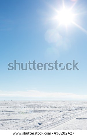 endless snow area and traces of a snowmobile - stock photo