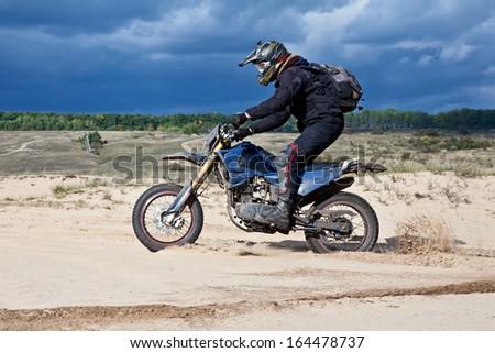 Enduro bike rider driving across the desert - stock photo